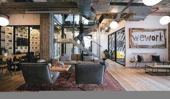 A WeWork co-working space in Tel Aviv. The picture shows a spacious, open area with a number of seating options, with wood floors, Oriental and sleek wood and upholstered furniture.