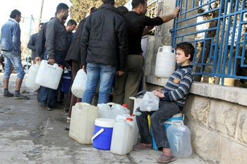 A boy waits to fill water containers while residents wait in line in Bab Neirab, Aleppo, February 2016.