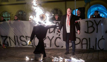 Piotr Rybak setting fire to a Jewish effigy during a rally against Muslim immigration.