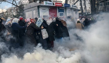 A group of women, as Turkish anti-riot police officers use tear gas to disperse demonstrators outside the Turkish daily newspaper Zaman, Istanbul, March 5, 2016.