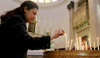 A woman lights a candle in memory of Italian PhD student Guilio Regeni, at Saint Joseph's Roman Catholic Church in Cairo, Egypt, March 5, 2016.