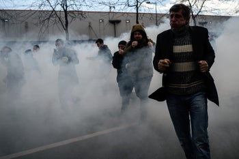 Men run as Turkish anti-riot police officers use tear gas to disperse supporters outside the daily newspaper Zaman in Istanbul, March 5, 2016.