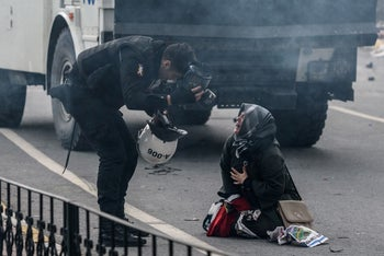 A police officer bends down near a woman crying in the street as Turkish anti-riot police officers use tear gas to disperse protesters, Istanbul, March 5, 2016.