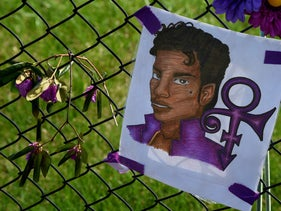 A Prince portrait and flowers left by fans outside the Paisley Park compound Minneapolis, Minnesota, on April 23, 2016.