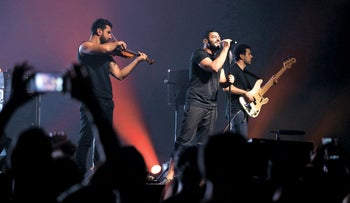 Hamed Sinno (C), the lead singer of Lebanese alternative rock band Mashrou' Leila, performs with his band during a concert in Beirut, Lebanon, August 6, 2015.