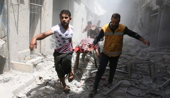 Syrian men carry a body on a stretcher amid the rubble of destroyed buildings following a reported air strike on the rebel-held neighborhood of Al-Qatarji in Aleppo,Syria, Apr. 29, 2016.