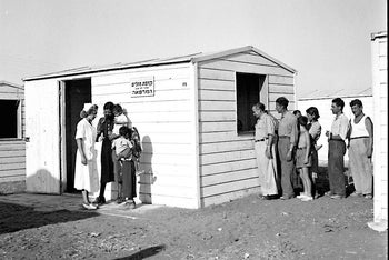 Residents of a transit camp near Tel Aviv light up outside a clinic in 1949.
