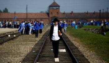 """A man walks on the railway tracks in the former Nazi death camp of Auschwitz-Birkenau as part of the annual """"March of the Living"""" to commemorate the Holocaust, May 5, 2016."""