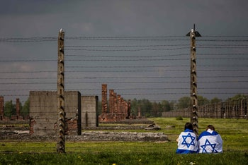 Visitors to the former Auschwitz-Birkenau Nazi death camp in Poland drape themselves in the Israeli flag, May 5, 2016.