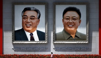 A woman walks past giant portraits of the late North Korean leaders Kim Il Sung and Kim Jong Il in Pyongyang, North Korea, May 7, 2016.