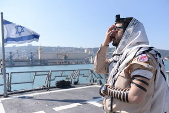 An Israeli soldier praying, wrapped in a prayer shawl - that is white with black stripes. In contrast to the thinking centuries ago, not all tallits are white with blue stripes.