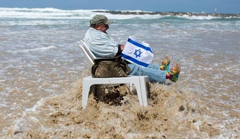 The Israeli flag: On Independence Day, a lot of Israelis drive with a flag attached to the car. This man on the beach went one better.