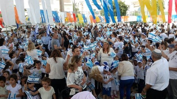 Children in the community of Gan Yavneh celebrate Israel's 68th Independence Day early, waving Israeli flags.