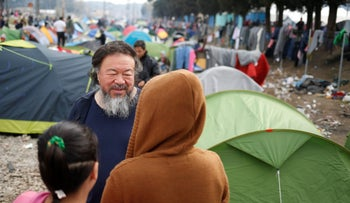 Chinese dissident artist Ai Weiwei talks with migrants in a makeshift camp on the Greek-Macedonian border, March 11, 2016.
