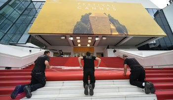 Staff members laying out the red carpet outside the Palais des Festivals in Cannes on May 10, 2016 on the eve of the opening ceremony of the 69th Cannes Film Festival.