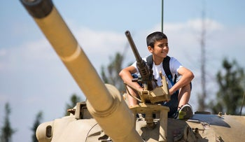A child sits on top of a tank at the Armored Corps memorial in Latrun after a Memorial Day commemoration ceremony, May 11, 2016.