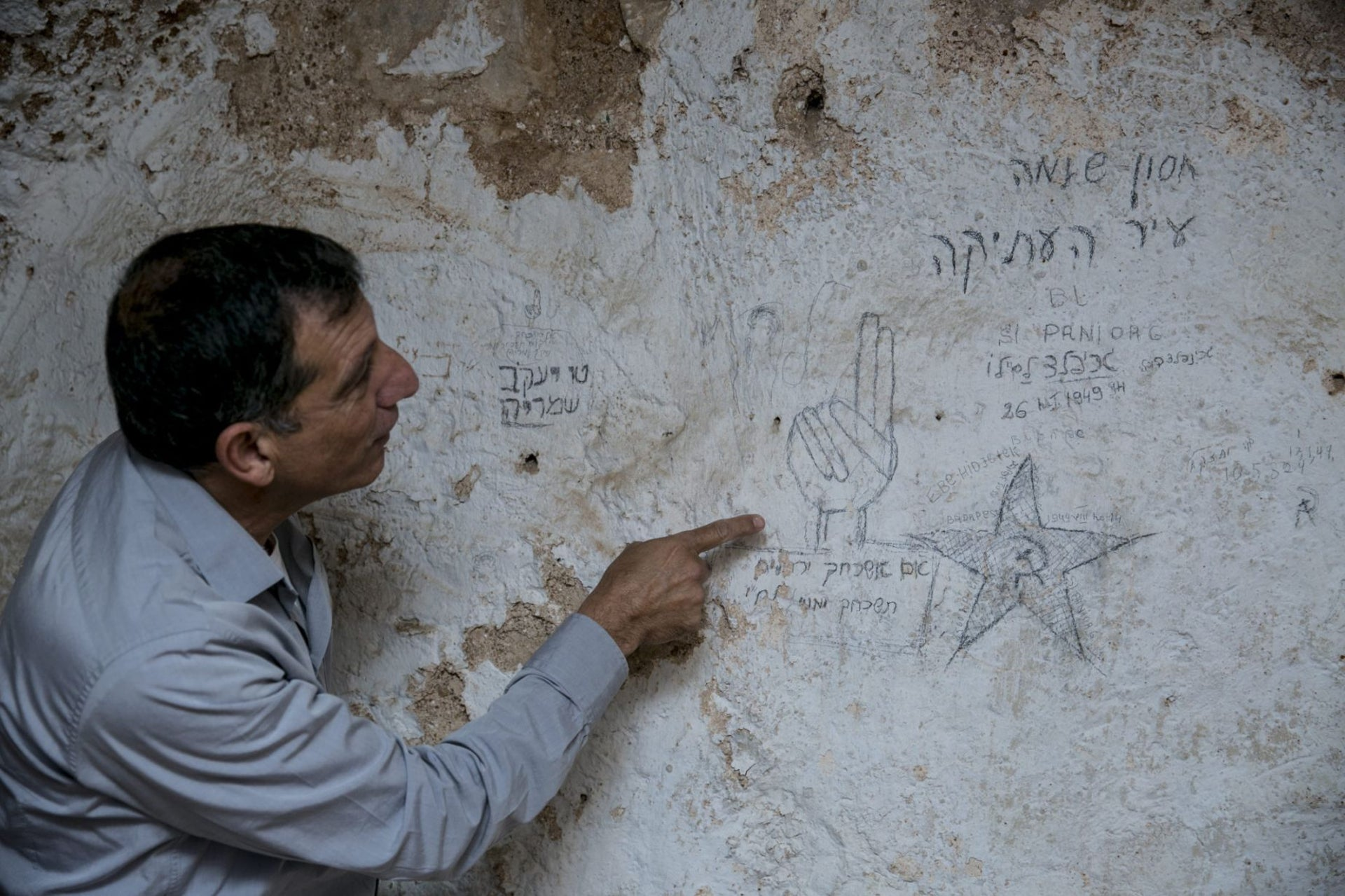 A man points to nationalist and communist graffiti left by Lehi fighters, Jerusalem, May 2016.
