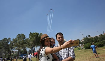 Israelis take a selfie in Tel Aviv, against the backdrop of the IAF airshow, May 12, 2016.