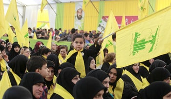 A girl waves a Hezbollah flag during a commemoration service marking the death of Ali Fayyad, a senior Hezbollah commander killed in Syria, in southern Lebanon, March 6, 2016.