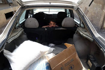 A Syrian boy sits in his family's car after they received aid provided by the UN World Food Program, May 11, 2016.
