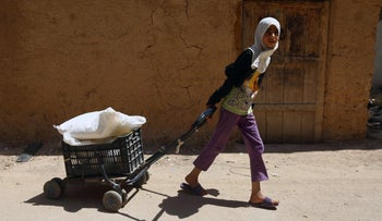 A Syrian girl in Damascus pulls a cart with food after receiving aid from the UN World Food Program, May 11, 2016.