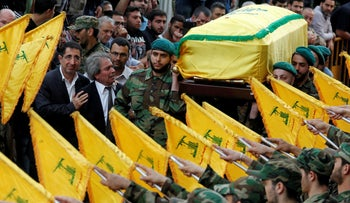 Hezbollah Industry Minister Hussein Hajj Hassan (L) comforts the brother of Hezbollah's Mustafa Badreddine, as Hezbollah members carry his coffin during his funeral in Beirut, Lebanon, May 13, 2016.