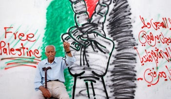 Mohammed Shehadeh, 86, holds a key in front of a mural ahead of the 68th anniversary of Nakba, in Qalandiyah refugee camp, May 14, 2016.