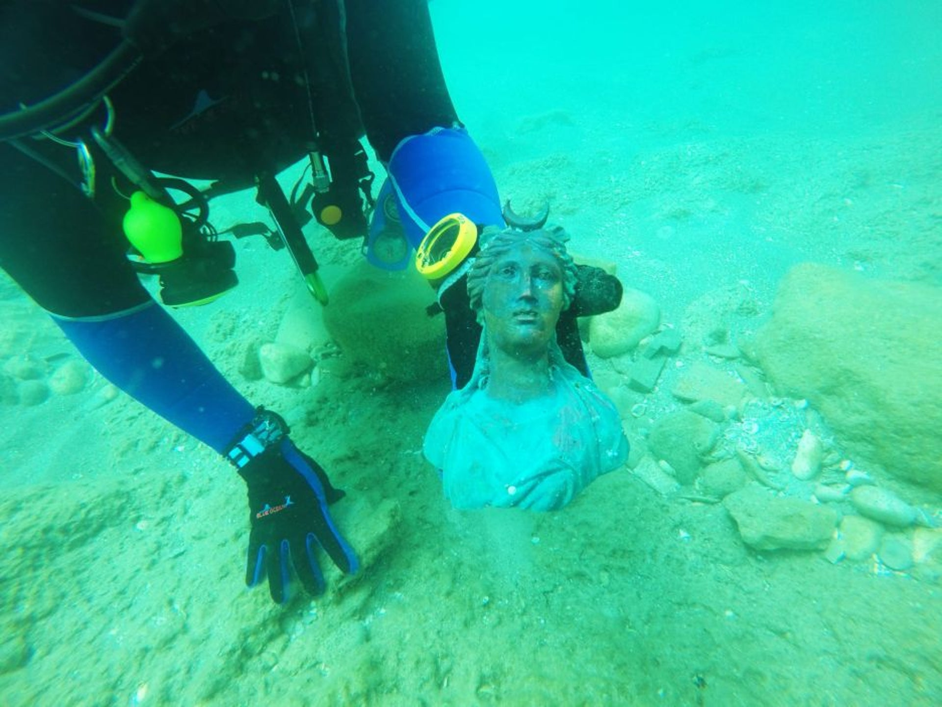 A diver removing a bronze sculpture thought to be some 1,600 years old, found on the seabed of Caesarea's harbor in May, 2016.
