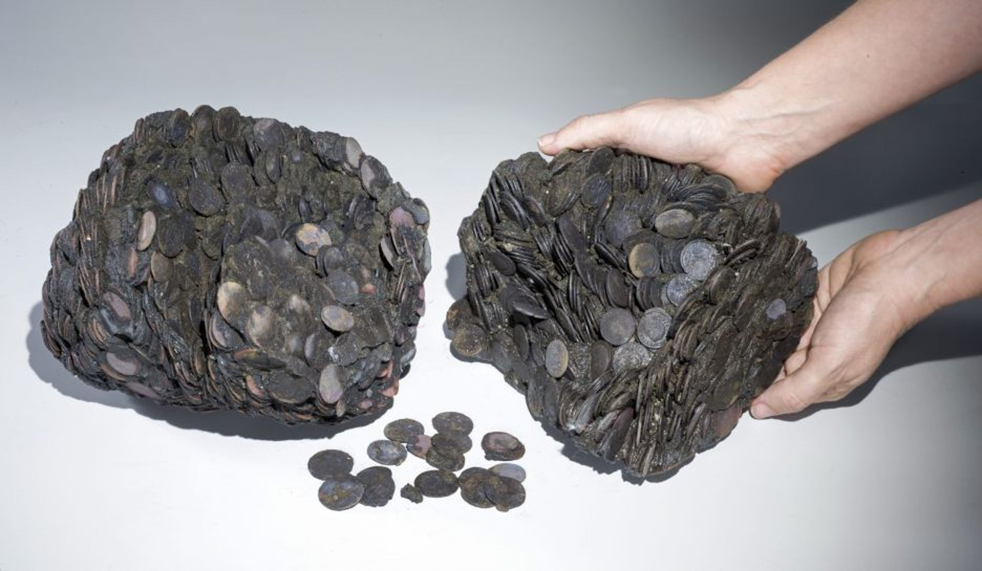 Clumps of coins discovered in the harbor of Caesarea in May, 2016, in the shape of the ceramic vessel in which they were transported before they oxidized and became stuck together.