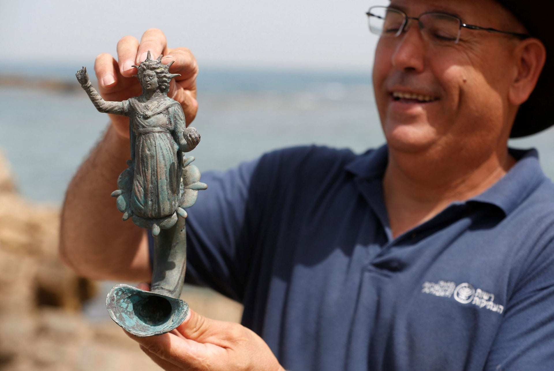 Jacob Sharvit, director of the Marine Archaeology Unit of the Israel Antiquities Authority, holds a part of a statue, which the IAA estimates to be around 1600 years old, after it was recovered from a merchant ship in Caesarea, May 16, 2016.