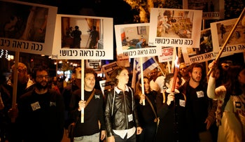 Breaking the Silence activists hold signs saying 'this is what the occupation looks like'  at a rally against incitement, Tel Aviv, December 2015.