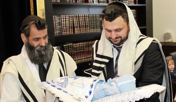Moishe Furer a rabbinical student in Berlin holding his son Elchanan at a circumcision ceremony in Berlin, Germany, June 29, 2012.