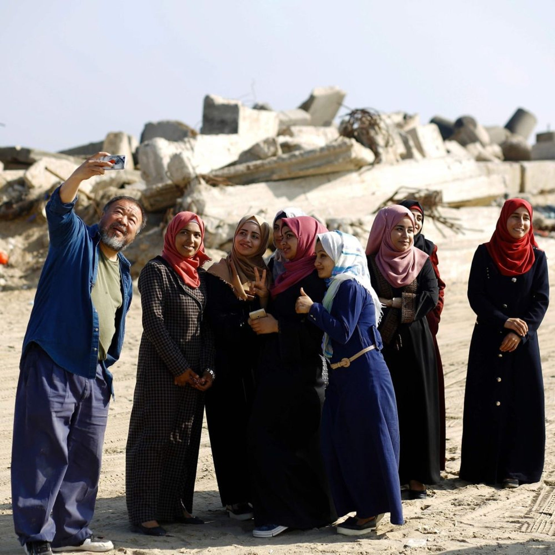 Chinese artist Ai Weiwei posing with women students in Gaza City, May 12, 2016.