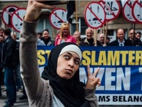 The selfie of Zakia Belkhiri taking a selfie in front of an anti-Islam demonstration.