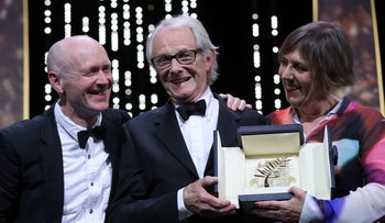 British director Ken Loach (C) celebrates on stage next to British screenwriter Paul Laverty (L) and British producer Rebecca O'Brien after being awarded with the Palme d'Or, May 22, 2016.