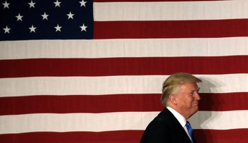 U.S. Republican presidential candidate Donald Trump walks past an American flag at a fundraising event, May 19, 2016.