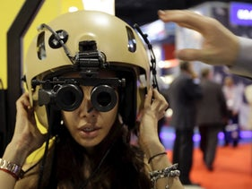 A visitor tries on an Aviation Night Vision Imaging System at the Elbit Systems booth at the Singapore Airshow, February 14, 2012.