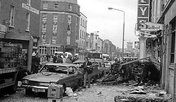 Talbot Street, showing the destruction of the second car bomb, May 17, 1974. The street is covered in debris and a parked car has shattered windows. A bomb allegedly planted by the loyalist Ulster Volunteer Force exploded, killing 14. Nobody has ever been charged.