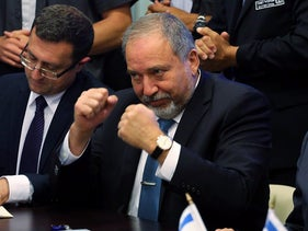 Avigdor Lieberman, head of far-right Yisrael Beitenu party, (L) sits next to Israeli Prime Minister Benjamin Netanyahu as they sign a coalition deal to broaden the government's parliamentary majority, at the Knesset, the Israeli parliament in Jerusalem May 25, 2016.