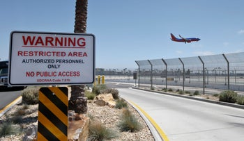 A commercial airliner lands at San Diego International Airport, where multiple razor wire topped fences are designed to secure the airport grounds, May 13, 2016.