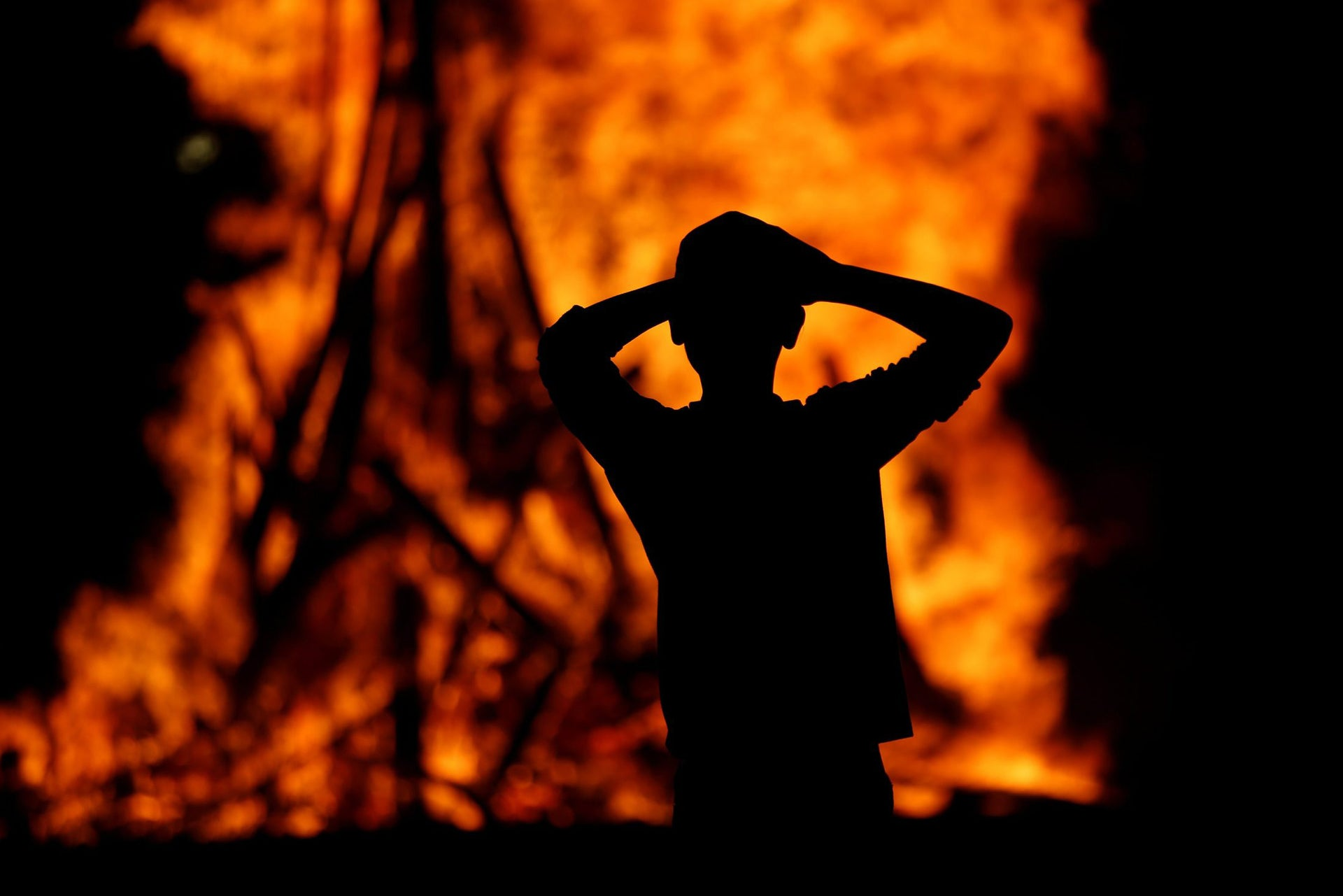 An Ultra-Orthodox Jewish boy stands around a bonfire as he celebrates the Jewish holiday of Lag Ba'Omer in the city of Ashdod, Israel May 25, 2016.