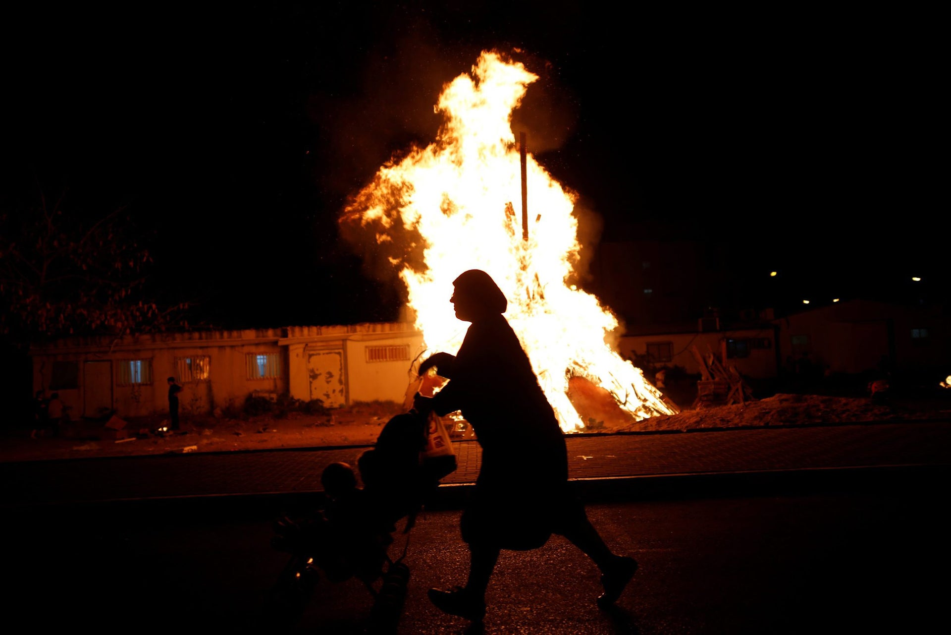 An Ultra-Orthodox Jewish woman walks with a stroller near a bonfire, as she celebrates the Jewish holiday of Lag Ba'Omer in the city of Ashdod, Israel May 25, 2016.