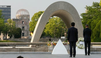 Japanese Prime Minister Shinzo Abe (2nd R) looks on as U.S. President Barack Obama (R) lays a wreath during a visit to the Hiroshima Peace Memorial Park in Hiroshima on May 27, 2016.