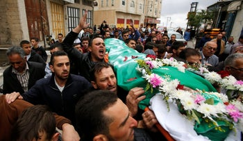 Mourners carry the body of Palestinian assailant Abdel Fattah al-Sharif, who was shot and killed after being wounded last March by an Israeli soldier, during his funeral in Hebron, May 28, 2016.