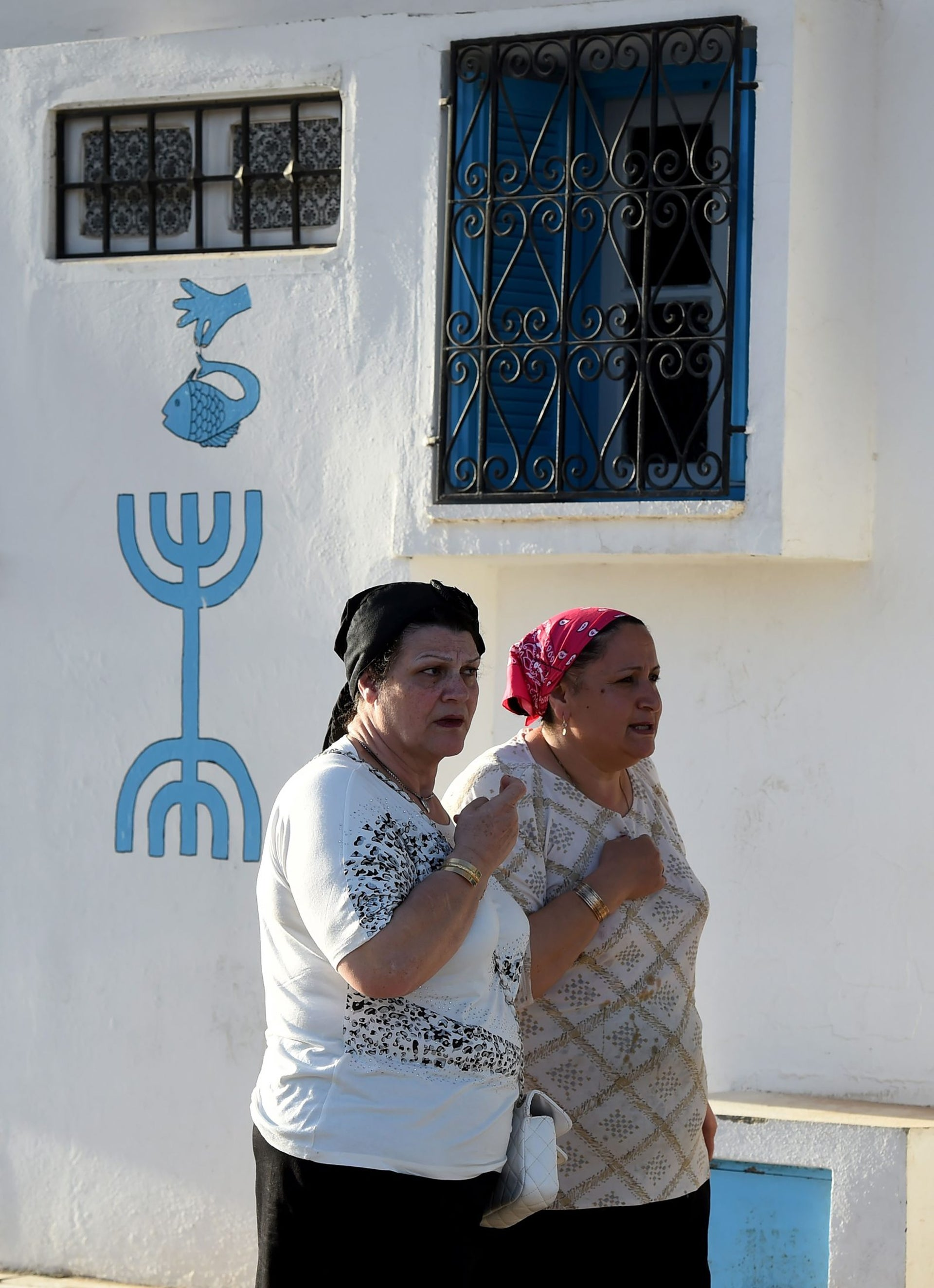 Tunisian Jewish women walk in the village of Hara Kebira on the Tunisian resort island of Djerba one day before the start of a two-day annual pilgrimage, on May 24, 2016.