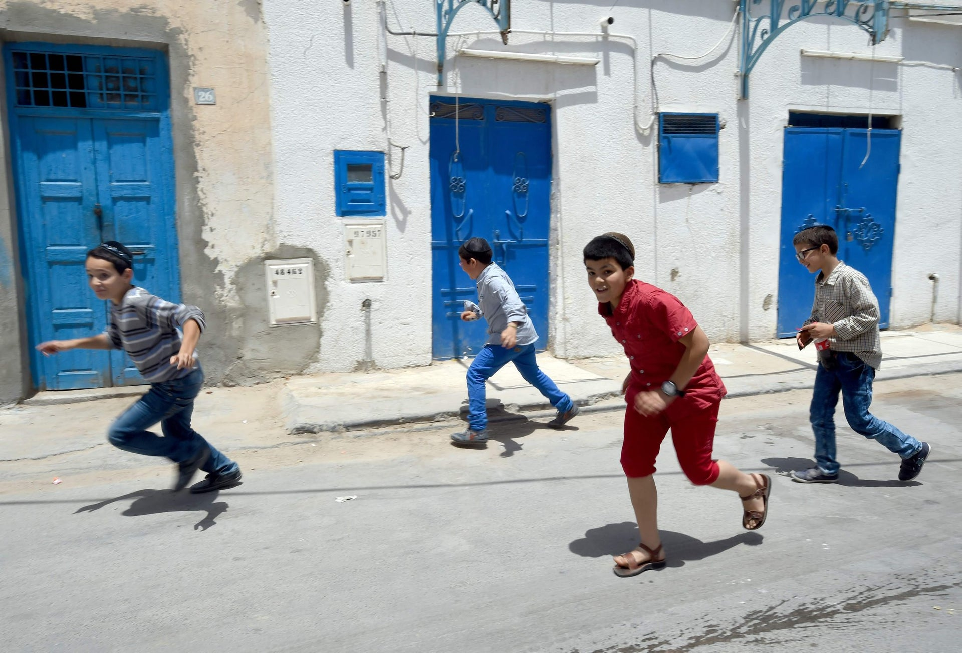Tunisian Jewish youths play in the streets of Hara Kebira, the main jewish quarter of the Tunisian resort island of Djerba, after attending a ceremony at the Ghriba synagogue on the during the annual Jewish pilgrimage on May 26, 2016.