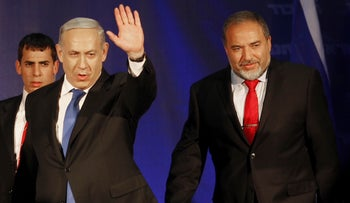In this Wednesday, Jan. 23, 2013, file photo, Israel's Prime Minister Benjamin Netanyahu and former Foreign Minister Avigdor Lieberman greet their supporters in Tel Aviv, Israel.