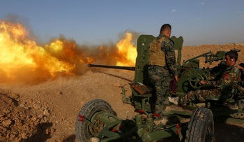 Iraqi Kurdish Peshmerga fighters fire an anti-tank cannon on the front line near Hasan Sham village, some 45 kilometres east of the city of Mosul, during an operation aimed at retaking areas from the Islamic State group on May 29, 2016.
