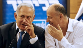 Prime Minister Benjamin Netanyahu chats with coalition chairman Tzahi Hanegbi as they attend a Likud meeting, Jerusalem, Israel, March 28, 2016.