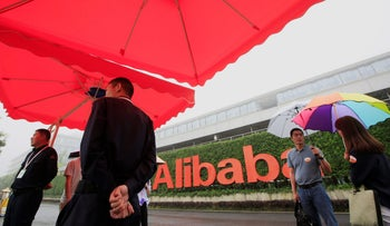 People stand near a sign of Alibaba Group at its campus in Hangzhou, Zhejiang Province, China, May 27, 2016.